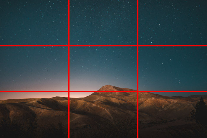 A mountainous scene with a stunning star filled night sky above, with the rule of thirds composition grid overlayed