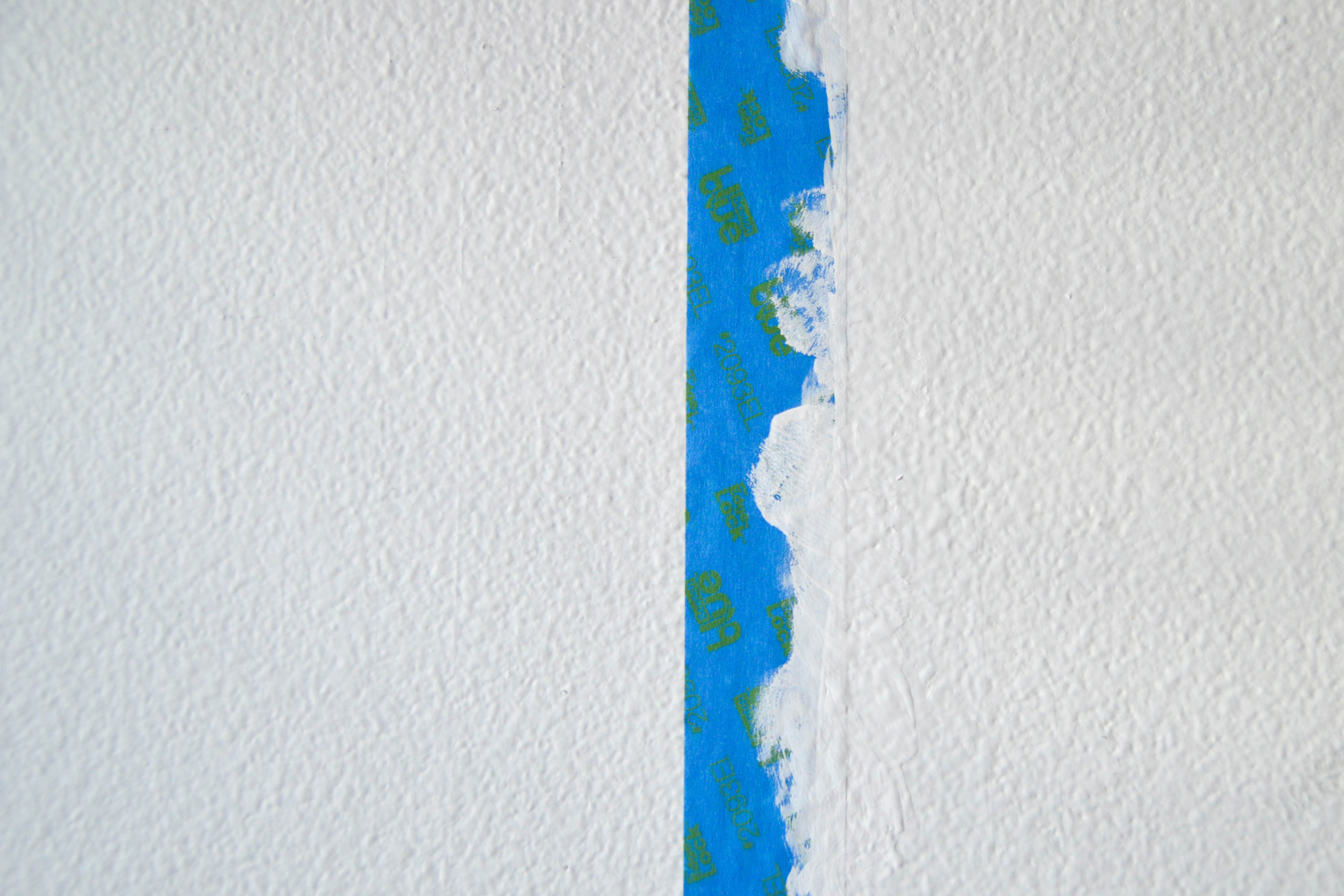 A white wall with blue paint tape